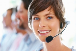 Closeup of attractive female executive wearing headset with team in blur background
